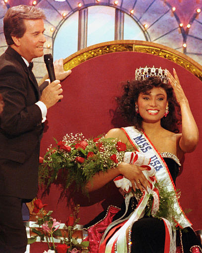 Miss Michigan Carole Gist, of Detroit, adjusts her crown while seated on the throne after being named Miss USA 1990 in Wichita, Kansas, Friday night, March 2, 1990. Standing at left is Dick Clark.  (AP Photo/Cliff Schiappa)
