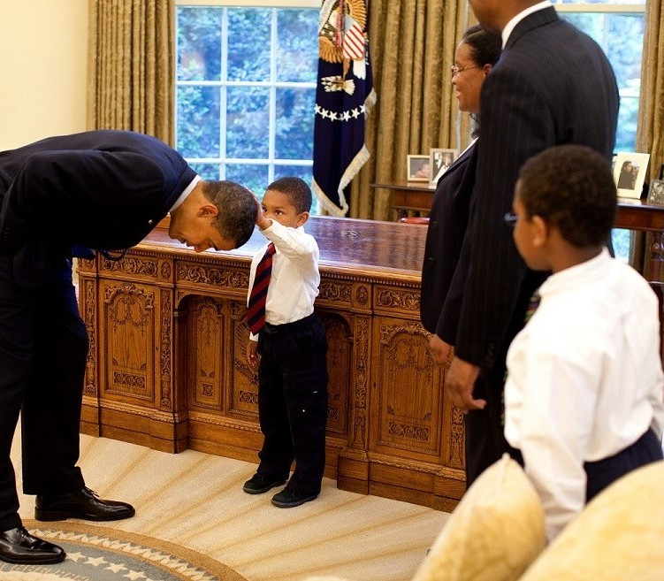 President Barack Obama bends over so the son of a White House staff member can pat his head during a visit to the Oval Office May 8, 2009. Official White House Photo by Pete Souza. This official White House photograph is being made available for publication by news organizations and/or for personal use printing by the subject(s) of the photograph. The photograph may not be manipulated in any way or used in materials, advertisements, products, or promotions that in any way suggest approval or endorsement of the President, the First Family, or the White House.